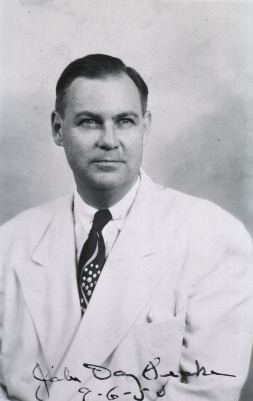 <p>Head and shoulders, full face, wearing white coat.</p>