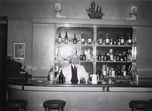 <p>An elderly male bartender wearing a light jacket and dark vest and tie poses behind a bar.  He holds a glass in one hand and a bottle of alcohol in another.</p>