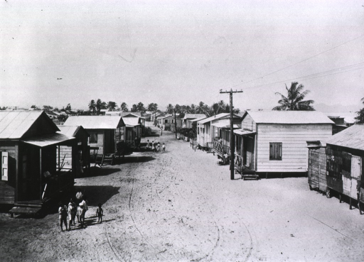 <p>View down a sandy road flanked by small wooden houses with black children standing in front of a house in the foreground; possibly in Puerto Rico?</p>