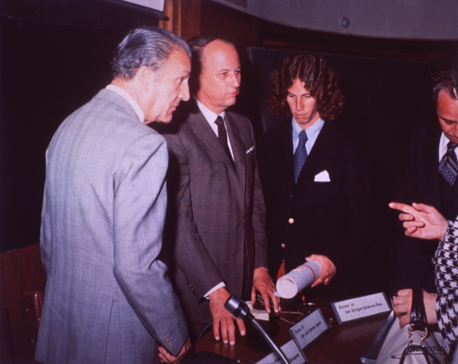 <p>Donald S. Fredrickson is standing behind a table between Francisco Vivanco and Eric Fredrickson.  On the table is a headset, name plates, a microphone, and a medallion case.  In the background there is a blackboard on the wall with a movie screen above it.  A blackboard on an easle is behind Eric Fredrickson.  Eric Fredrickson is holding a white paper rolled with an elastic band around it.   Dr. Fredrickson appears to be listening to a woman standing in front of him on the other side of the table who is partially in the picture.</p>