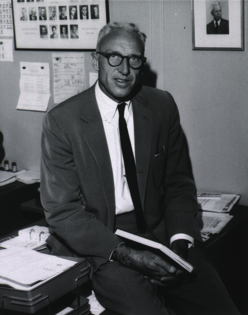 <p>Three fourths length, full face; seated on desk, book in hands; wearing glasses.</p>