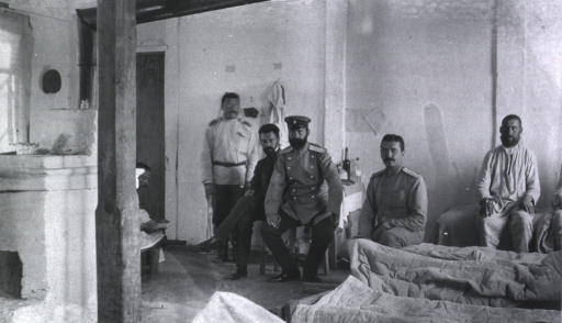 <p>The Commanding Surgeon of Military Mobile Hospital No. 84 sitting in a ward with patients and personnel.</p>