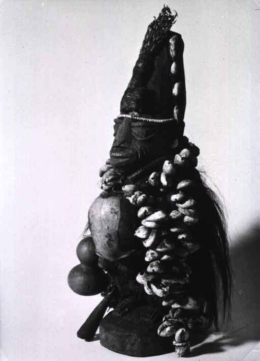 <p>Wooden statue adorned with hair, shells, beads, and a sheaf of some plant material.</p>