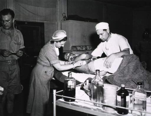 <p>A female medical personnel cleans the lower back wound of a serviceman.  Two other male medical personnel are seen in the operating room.</p>