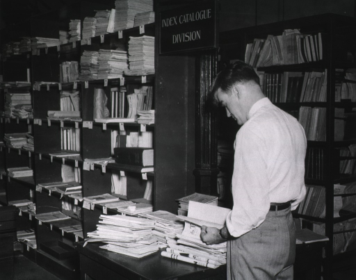 <p>Interior view:  Harold Koehler is looking at material on a table at the end of a shelf of serials.</p>