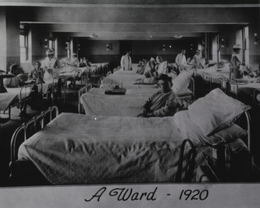 <p>Interior view: a hospital ward with three rows of beds; nurses and physicians are making the rounds; many patients are sitting next to their beds. A model ship sits on one bed.</p>