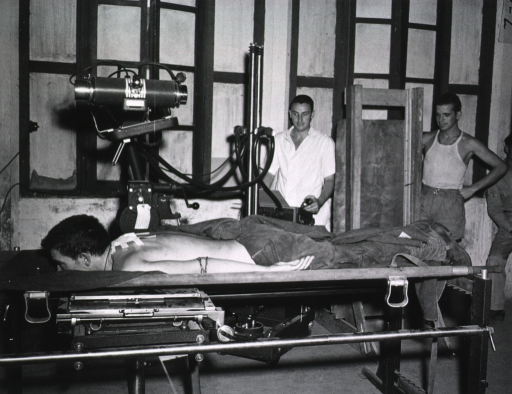 <p>A male patient lies on his stomach under an X-ray machine. A male technician operates the machine, while two other servicemen observe.</p>
