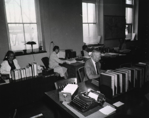 <p>Interior view: Staff members seated at desks.  Underwood typewriter is in the foreground.</p>
