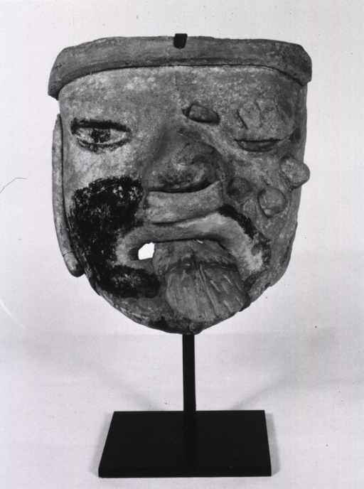 <p>Sculpture:  Clay mask, with protruding tongue, exhibiting postorbital tumefactions and ophthalmic defect.</p>