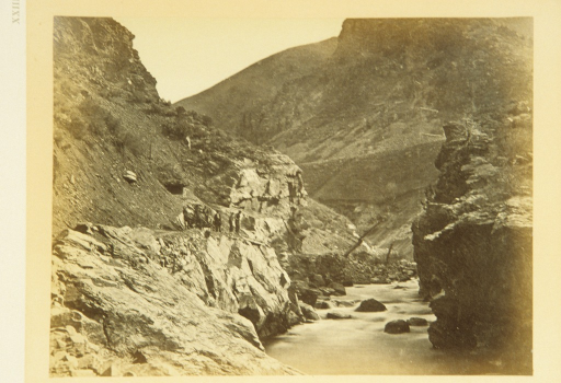 <p>View of rock formations. A river cuts through the mountains. Men on horses and on foot pose atop one of the rocky banks.</p>