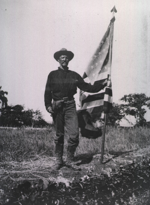 <p>Sergeant Porter stands holding an American flag at one of the trenches.</p>
