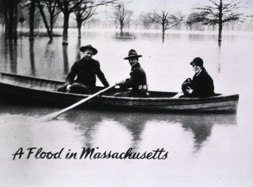 <p>Showing a nurse in a boat with two soldiers.  She is on her way to a patient during the flood in March 1926.  The boat is on the road between Springfield and Holyoke.  The normal bank of the Conn. River is indicated by line of trees in background.</p>