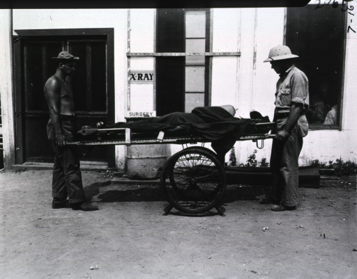 <p>Two servicemen transport a patient on a wheeled stretcher into a building. Next to the door of the building are posted signs that read:  &quot;X-ray&quot; and &quot;Surgery&quot;.</p>