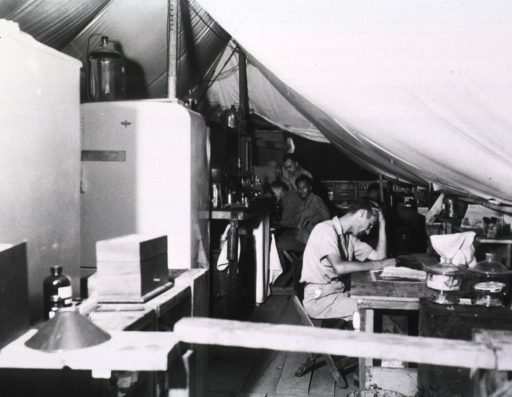 <p>Servicemen sit and work at various tables and desks in a tent.</p>