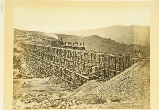 <p>View of a trestle bridge spanning a valley. Workers pose on the trestle bridge in front of a train engine that spews smoke. Rocks are piled in the foreground; mountains rise in the distance.</p>