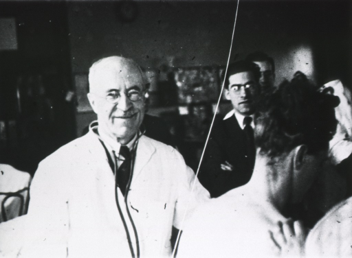 <p>Half-length, full face; with stethoscope; wearing white coat; in a room (clinic?) with other people present.</p>