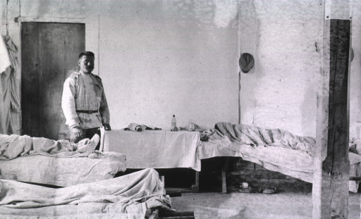 <p>A staff person standing in a ward at Military Mobile Hospital No. 84.</p>