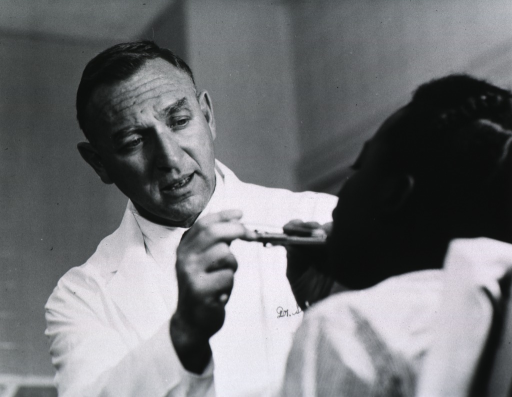 <p>Half length, full face; in lab coat, examining woman's throat.</p>
