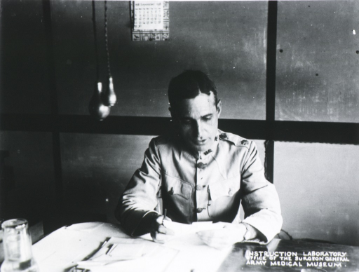 <p>Head and shoulders, seated at desk; wearing uniform (Major); reading.</p>