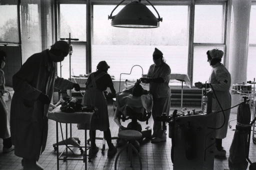 <p>Interior view of operating room: a patient is lying on the operating table; surgeons and nurses are preforming various tasks leading up to the operation.</p>