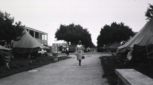 <p>Showing a nurse on a walkway between tents.</p>
