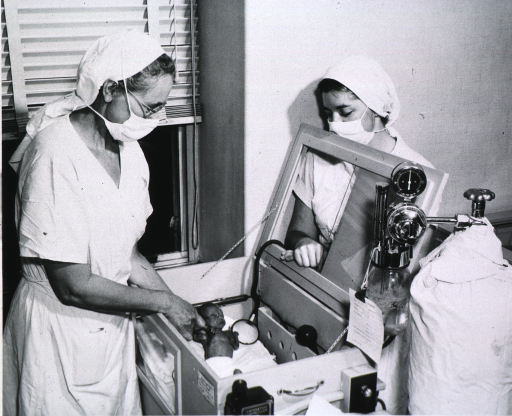 <p>View of nurses observing a premature infant in an incubator.</p>