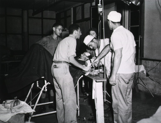 <p>An unconscious serviceman lies on an operating table while four servicemen and one woman tend to him.</p>