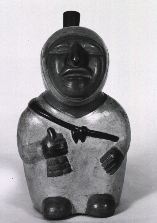 <p>Sculpture:  Spouted urn in the form of a Mochica individual holding a bell or rattle in right hand.  The treatment accorded to the eyes suggests blindness.</p>