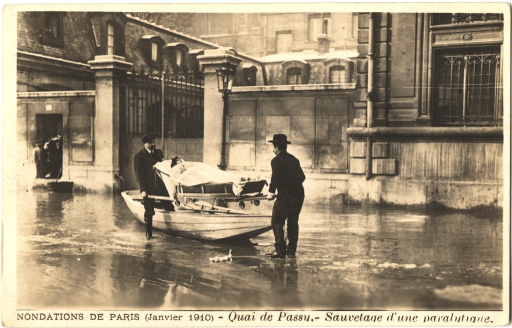 <p>Black and white photo of two men transporting a paralyzed patient by a boat at frozen wharf of Passy in Paris, France in January 1910.</p>