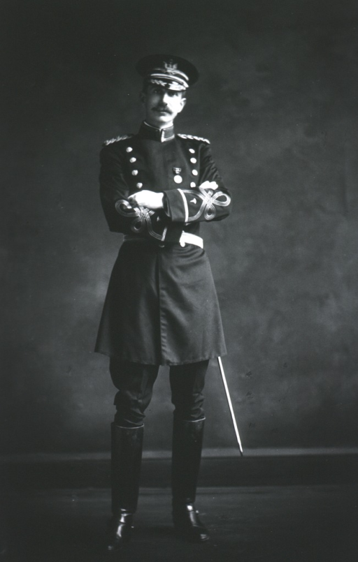 <p>Full length, standing, full face; wearing uniform with sword and cap; arms folded.</p>