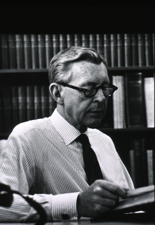 <p>Half length, turned to right, wearing glasses; seated at desk, reading book; in front of bookcase.</p>