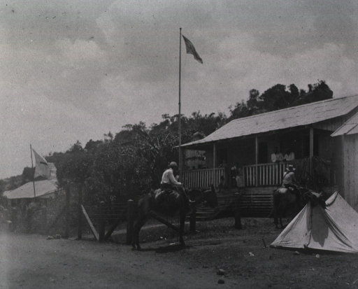 <p>View of two men on donkeys beside a pup tent in the front yard of a house.  Several people are on the front porch.</p>