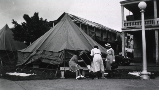 <p>Showing three nurses standing outside a tent.</p>