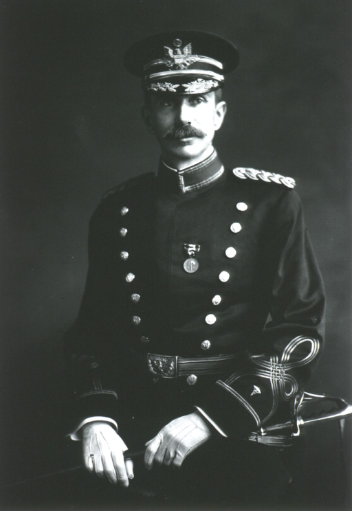 <p>Three-quarter length, seated, left pose, full face; wearing uniform and cap; holding sword across lap.</p>