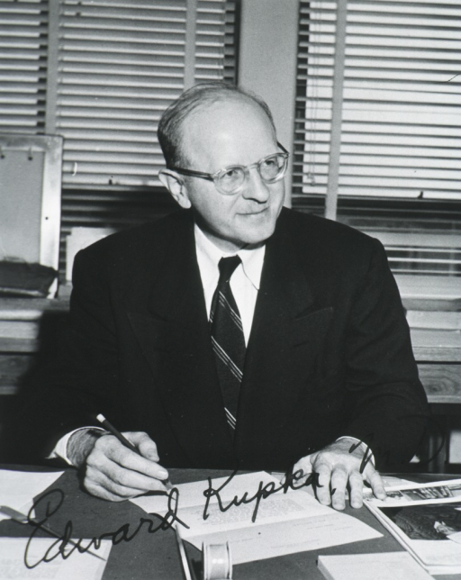 <p>Half-length, seated at desk, front pose, head turned to the right; wearing glasses; holding pencil.</p>