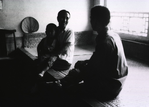 <p>A young man is chatting with a woman and her child in their home.</p>