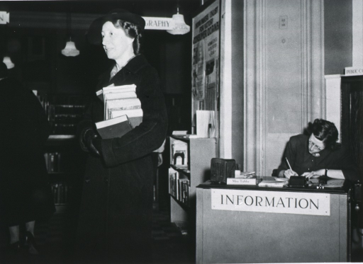 <p>Miss Gilpin seen here, with an armful of books, in the Montclair Library.  A Miss Tubby is seated at the Information desk.</p>