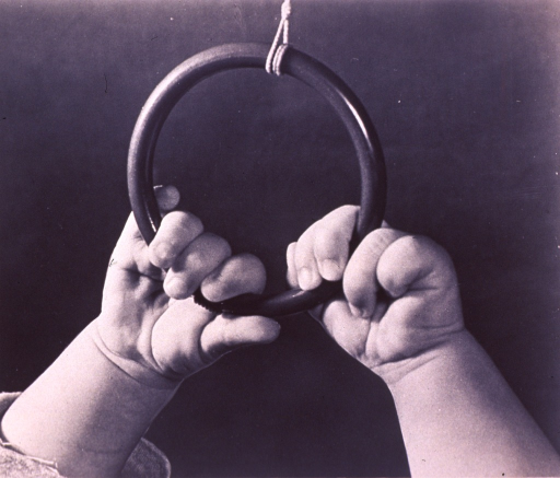 <p>Four month old hands grasping a ring hanging overhead.</p>