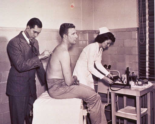 <p>A physician with a stethoscope is examining a patient sitting on a table; a nurse prepares to administer a blood pressure test.</p>