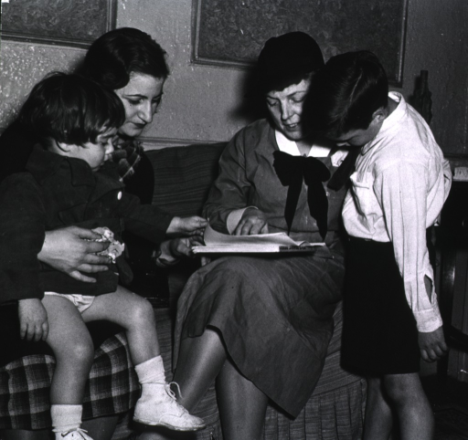 <p>A public health nurse seated on a sofa with a mother and her two children.</p>