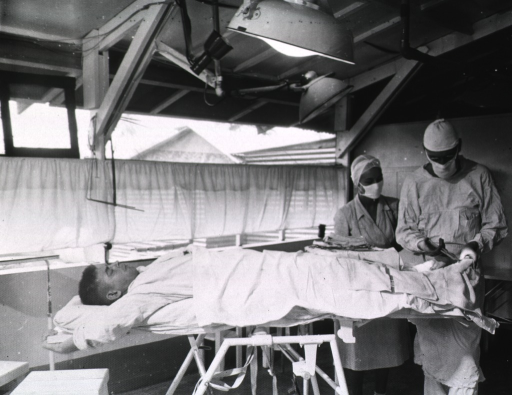<p>A doctor peforms a surgical procedure on the foot of a man.  A nurse attends the doctor.</p>