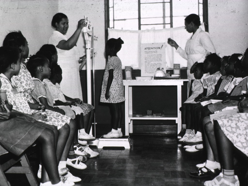 <p>An African American nurse is measuring a girls' weight while others wait their turn to have their height and weight measured.  In the background is a sign that describes tuberculin testing.</p>