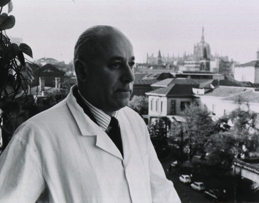 <p>Half-length, turned to right, wearing lab coat, standing outside, showing city in background.</p>
