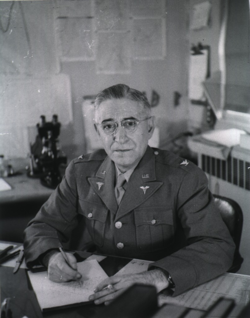 <p>Seated at desk, front pose, wearing uniform (Colonel).</p>