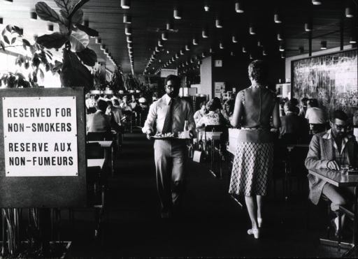 <p>Interior view of a restaurant with a sign posted stating section &quot;Reserved For Non-Smokers.&quot;</p>