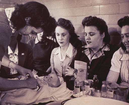 <p>An instructor demonstrates proper infant care procedures to a group of young women.</p>