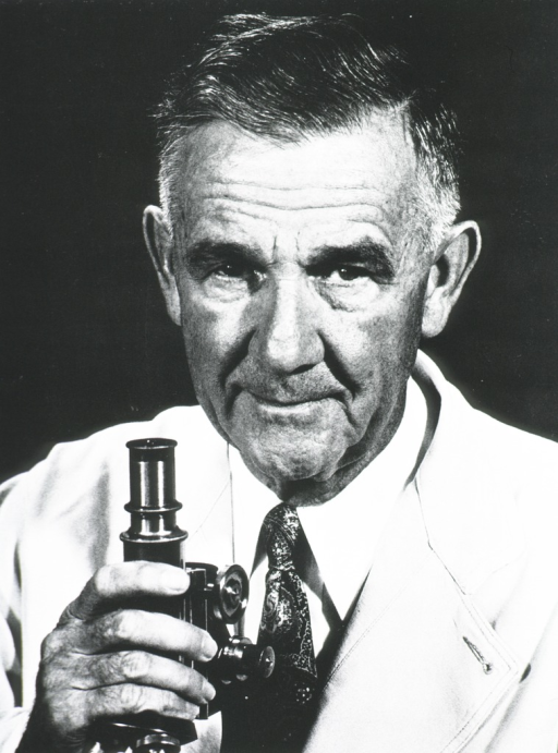 <p>Head and shoulders, full face, his right hand on a microscope.</p>