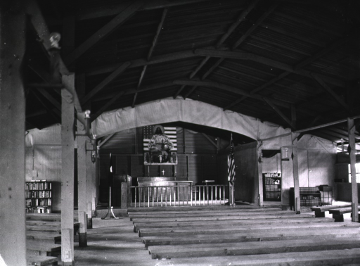 <p>View from the rear of a hospital chapel.  Rows of backless benches are positioned in front of a stage serving as the altar.  A painting of Christ hangs on the back wall.</p>