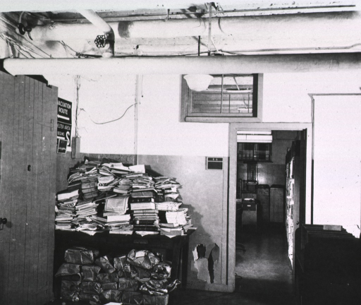 <p>Interior view: Publications are piled on top of, and underneath, a table.  Above the table are signs leading to the shelter area and the evacuation route.  Next to the table is a hole in the wall.</p>
