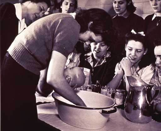 <p>Infant bathing techniques are demonstrated to a group of young women.</p>